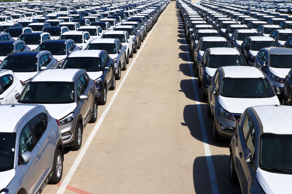 Rows of new cars in car storage covered in protective white sheet