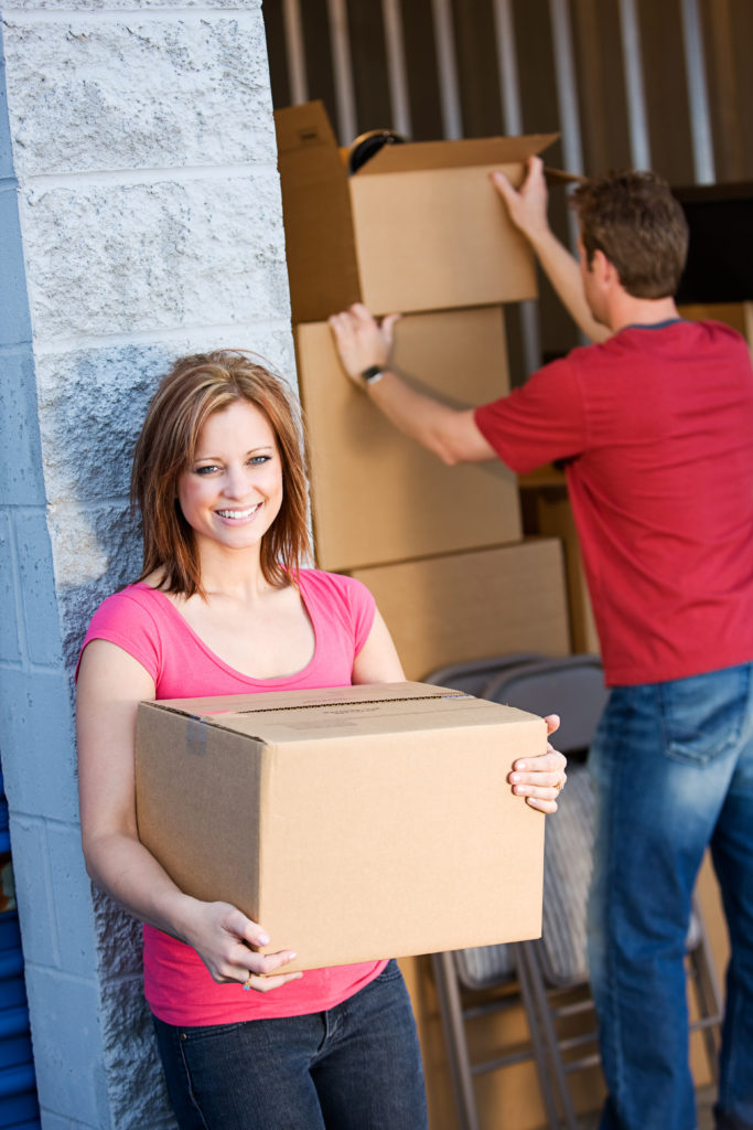 Caucasian man and woman with various props at a typical commercial storage unit.